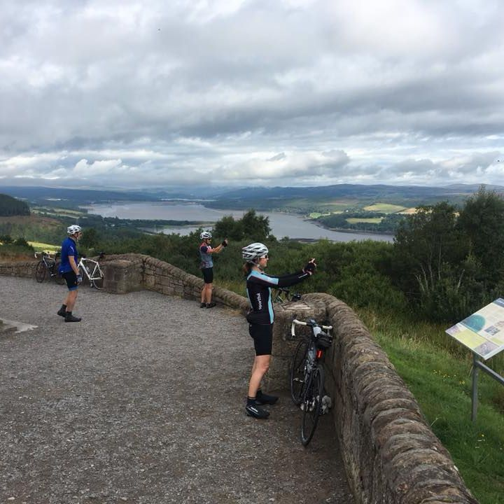 people taking photo of a view in scotland