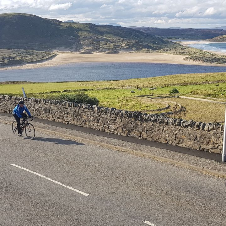 cyclists riding up hill with sea in background
