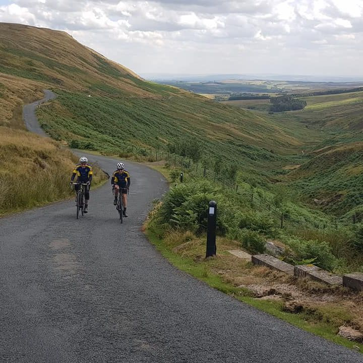 Cyclists riding up hill in Forest of Bowland