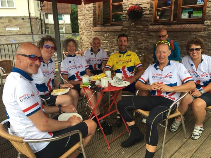 group of lejog cyclists sat at table and chairs eating lunch